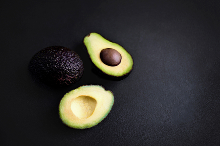 Avocado on a black background. Half of avocado close up. Top view. Copy space