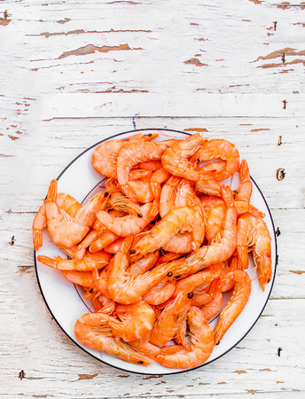 Cooked fresh  shrimps on a white plate over old white wooden table with copy space, flat lay. Seafood healthy food concept Фото со стока