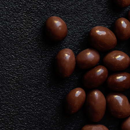 Chocolate candy background. Dark brown chocolate round candies on black concrete background  top view, close up