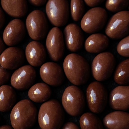 Chocolate candy textured background.  Dark brown chocolate round candies on black concrete background  top view, close up