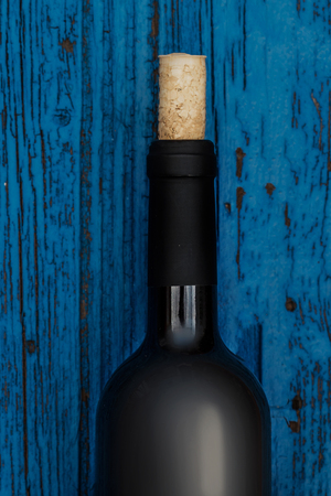 Bottle of wine on blue wooden   background  with copyspace, Wine degustation concept Stock Photo
