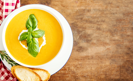 Pumpkin and carrot soup with  croutons on rustic wooden background. Autumn Cream Soup Top view. Copy space. Stock Photo