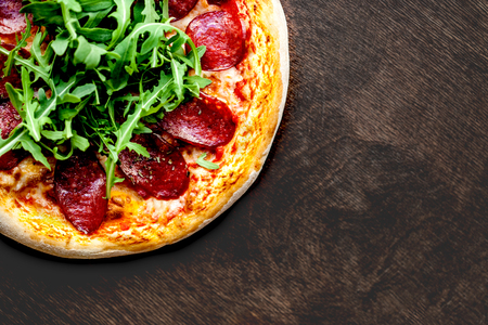 Tasty Hot  italian pizza with pepperoni served on old wooden table. Pizza with salami, bacon, arugula  and  cheese. Copy-space. Flat lay