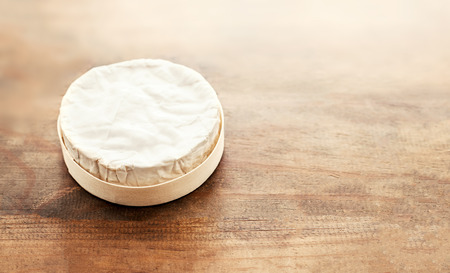 Cheese camembert on wooden desk, top view. Soft creamy cheese Brie with copy space