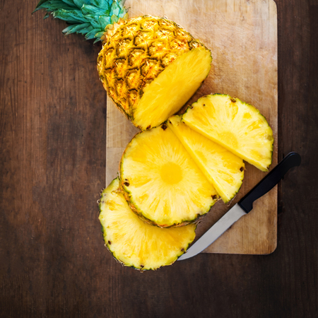 Pineapple on wood texture background. Whole and sliced tropical pineapple on wooden cutting board  with copy space. Flat lay Stock Photo