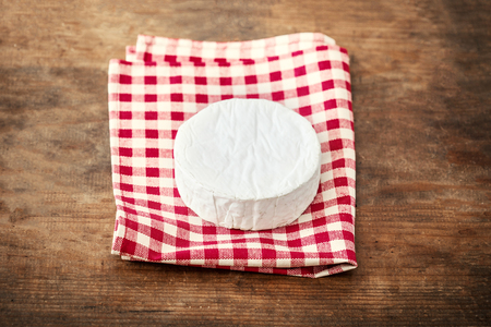 White soft Cheese Brie on wooden background, top view. Creamy cheese with copy space