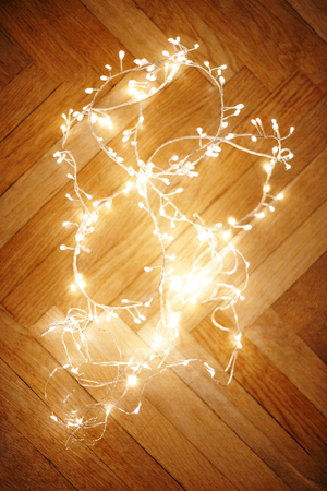 Christmas lights on dark  wooden background. Defocused Christmas garland, copyspace Stock Photo