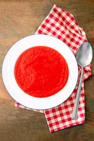 Tomato soup on wooden table, top view. Ready-to-eat