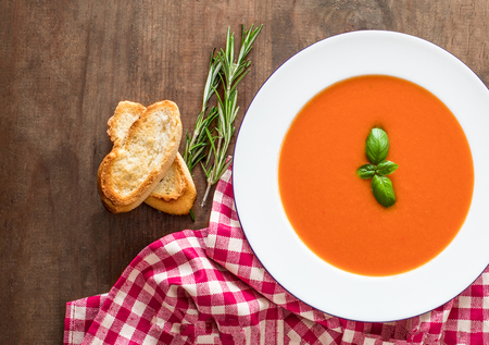 Vegetarian autumn Tomato soup with bread on wooden table, flat lay. Copy space Banque d'images