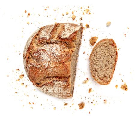 Geschnittenes Brot getrennt auf weißem Hintergrund. Krümel und frische Brotscheiben hautnah. Bäckerei, Lebensmittelkonzept. Ansicht von oben