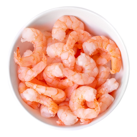 Peeled shrimps in a bowl isolated on white background. Top view
