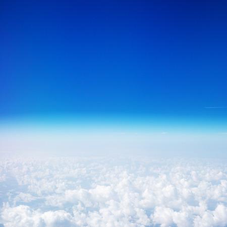 Schöner Himmel über den Wolken. Blick aus dem Flugzeugfenster mit blauem Himmel und flauschigen Wolken Standard-Bild