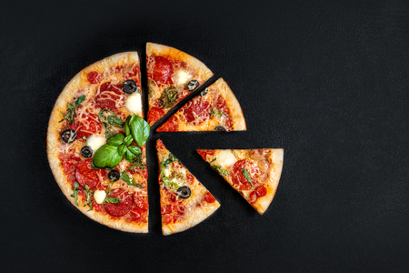 Flatbread pizza  with  slices on black background. Pepperoni Pizza. Copy space. Top view Banco de Imagens - 122107427