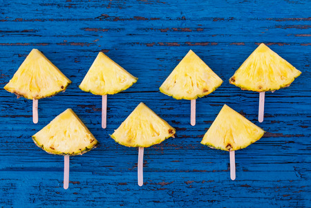 Pineapple  slice  on a blue rustic wood background. Flat lay. Tropical Summer concept Banco de Imagens - 122107682