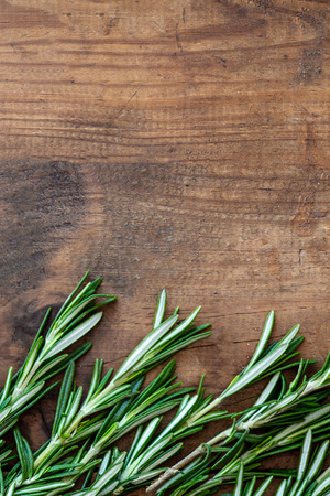 Rosemary herb on a wooden background, copyspace. Fresh rosemary Board. Top view Banco de Imagens - 122107691