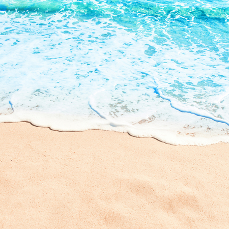 Blue ocean wave on sandy beach. Summer day and sand beach background concept.