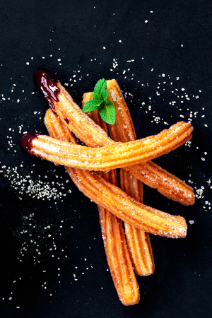 Churros with sugar and chocolate sauce on a black background. Traditional Spanish dessert. Top view Banco de Imagens
