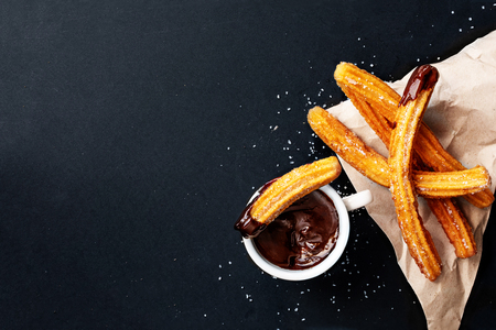 Churros with sugar dipped in chocolate sauce on a black background. Churro sticks. Fried dough pastry, top view 免版税图像