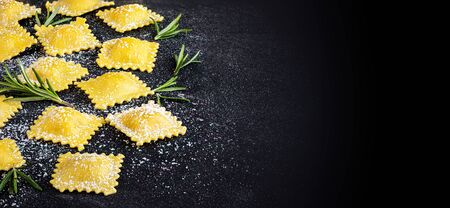 Raviolli with flour and herbs on dark background, top view.  Copy space. Italian Food Banco de Imagens