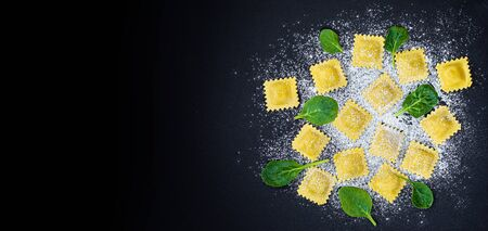 Fresh ravioli pasta with Spinach, flour and herbs on dark background, top view.  Italian Raviolli. Copy space. Banco de Imagens