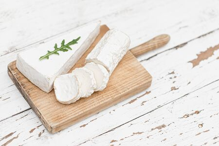 Wooden board with various cheese on white background. Cheese platter. Copy space