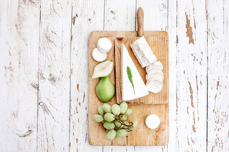 Cheese Board  with different cheese, pear and grapes on white  wooden background. Cheese platter Top view. Copy space