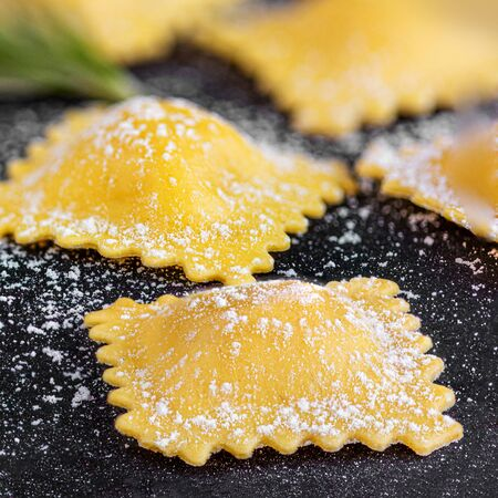Raviolli with flour and herbs on black background, close-up.  Italian Food Banco de Imagens