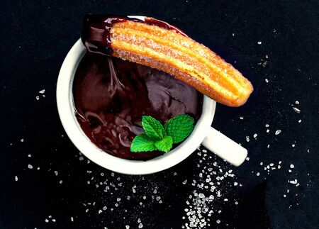 Churro with and chocolate sauce in a cup on a black background. Churro - traditional Spanish dessert. Top view