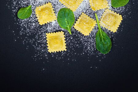 Fresh ravioli pasta with Spinach leaves, flour and herbs on black background, top view.  Italian Raviolli. Copy space. Banco de Imagens