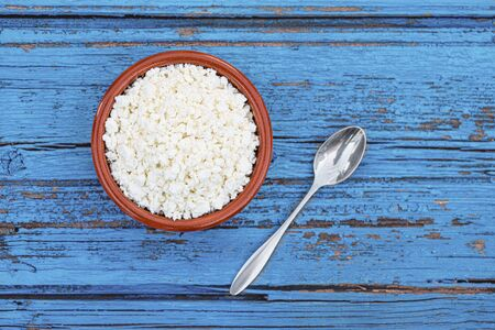Fresh Cottage cheese in a bowl on blue rustic wooden table. Top view