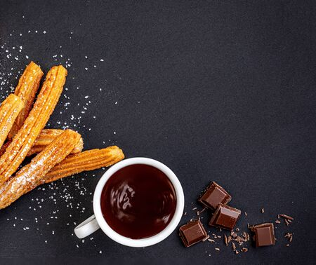 Churros with liquid chocolate. Churro - Fried dough pastry with sugar powder on black  background.