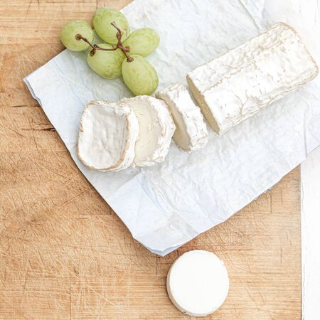 Cheese platter with different cheese and grapes on white  wooden background. Top view