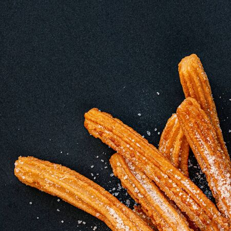 Churro on a black background. Traditional Spanish cusine. Churros in a paper bag with copy space. Top view