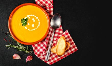Pumpkin soup on dark background. Bowl of tasty pumpkin  cream soup. Top view. Copy space Reklamní fotografie
