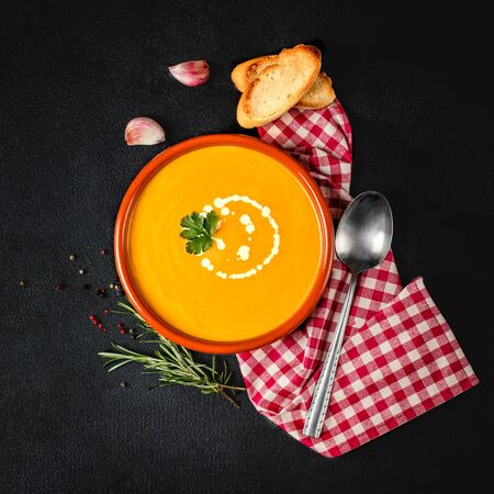 Pumpkin soup on dark background. Bowl of tasty pumpkin  cream soup with herbs, bread and red checkered tablecloth. Top view. Copy space