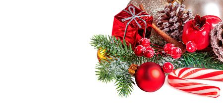 Christmas Card with a red ornament, golden balls, berries, fir tree, snow  and pine cones isolated on white background.  Winter holiday concept Reklamní fotografie - 129798611