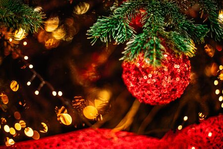 Christmas tree and  decorations with abstract sparkling lights. Red ball, golden bokeh lights, ribbon in dark tones