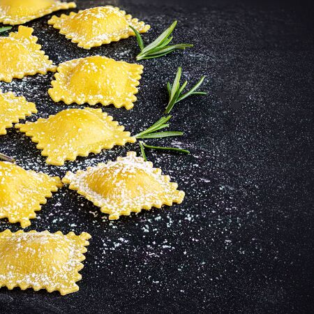 Raviolli with flour and herbs on dark background, top view.  Copy space. Italian Food Reklamní fotografie - 129798631