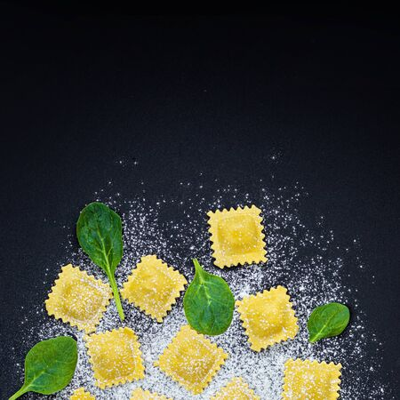 Fresh ravioli pasta with Spinach, flour and herbs on dark background, top view.  Italian Raviolli. Copy space. Reklamní fotografie