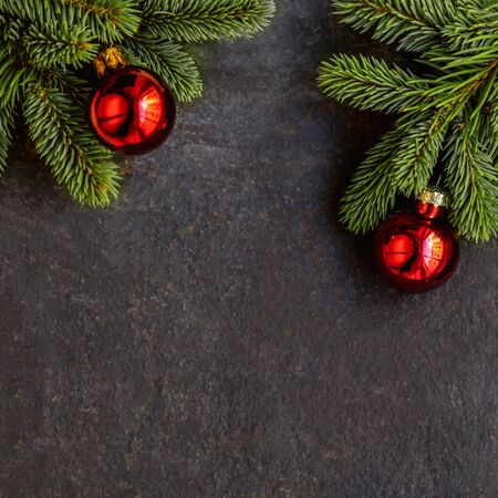 Christmas background with  fir tree and  festive decoration on dark black  board, copyspace