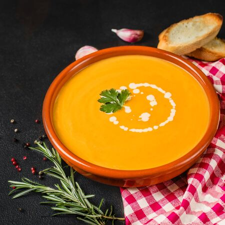 Pumpkin and carrot soup on black  stone background. Vegetarian soup in a rustic bowl with bread. Top view. Copy space Reklamní fotografie