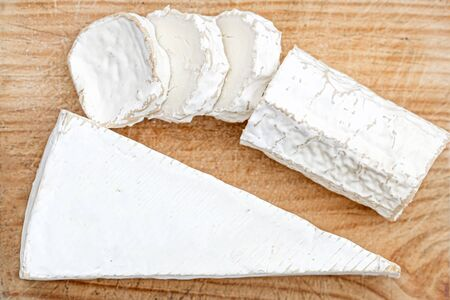 Wooden board with white goat cheese on bright background. Cheese platter