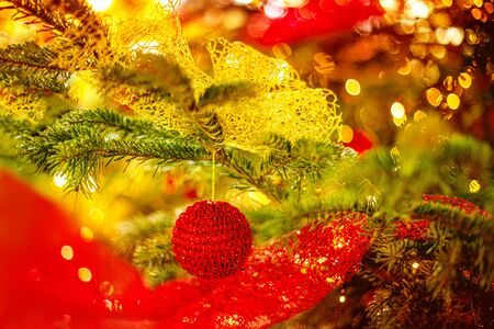 Christmas tree and Christmas decorations with red baubles and blurry golden bokeh lights. Happy New Year and Xmas Card