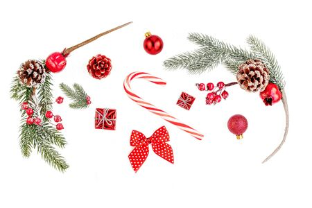 Christmas composition Isolated. Christmas  pine branches with red berries, balls, gifts and sweet cane on white background. Creative layout. Flat lay, Top view.