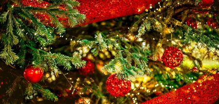 Christmas tree and Christmas decorations with hanging red baubles and golden sparkling lights. Happy New Year and Xmas Card