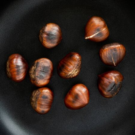 Chestnut on a black frying pan isolated on white background, top view. Roasted Chestnuts close up Imagens