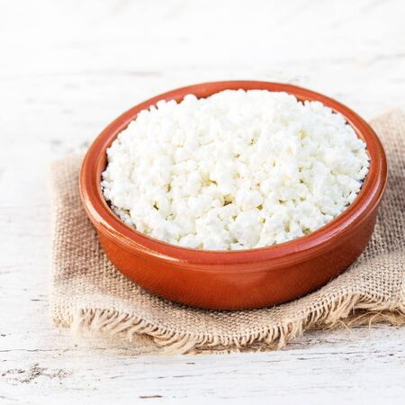 Homemade cottage cheese in a ceramic bowl on white old wooden table. Healthy food. Fresh dairy products. Close up