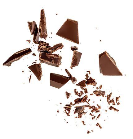 Fliegende dunkle Schokoladenstücke lokalisiert auf weißem Hintergrund. Schokoriegel, Späne und Kakaobrösel Ansicht von oben. Flach legen