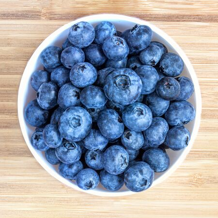 Blueberries on a wooden  background. Freshly picked blueberries in a white  bowl.  Top view