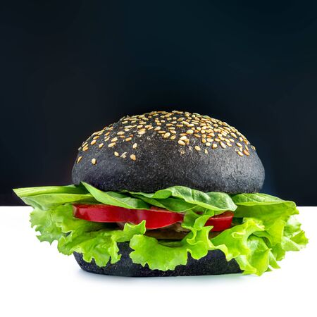 Tasty vegetarian burger with lettuce and vegetables isolated on white background. Black Burger.  Fast Food Banco de Imagens